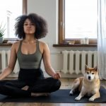 woman meditation on a yoga mat next to a dog